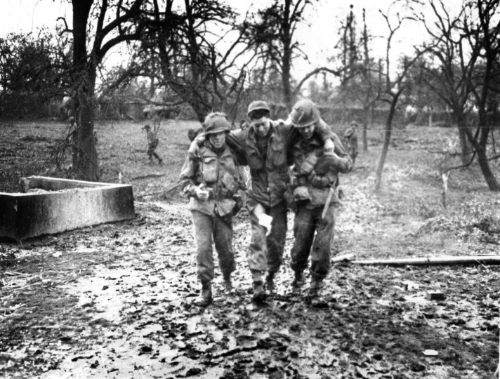 A wounded soldier of the Maryland 29th is helped to the rear during the Normandy offensive. (Holbrook Bradley/Baltimore Sun file photo)