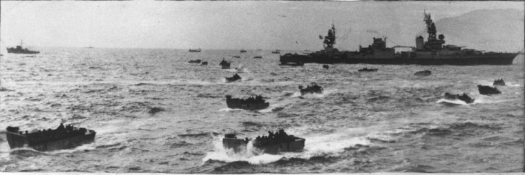 On June 6, 1944, U.S.S. cruiser Augusta sits off the Normandy shore as landing craft take soldiers of the Maryland 29th division to beaches. (US Army file photo)