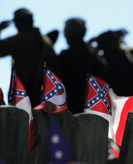 An honor guard removes their hats as many gather at Loudon Park Cemetery. (Doug Kapustin/for The Baltimore Sun)