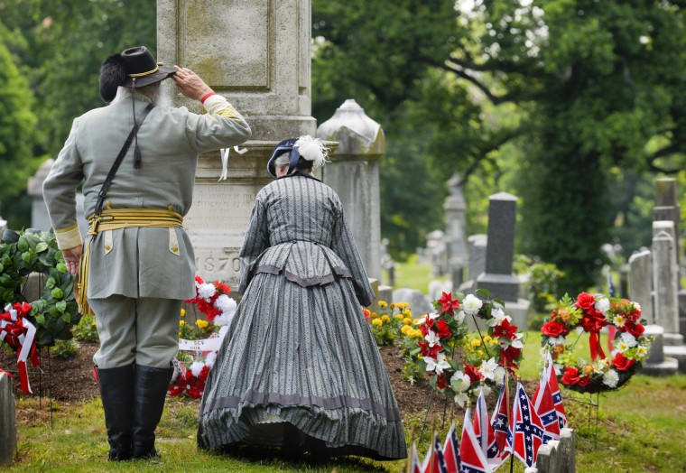 "Bob Parker and Liz Groszer lay a wreath at the ""Stonewall"" Jackson monument as many gather at Loudon Park Cemetery to attend the 141st commemoration of Confederate Memorial Day in Maryland. (Doug Kapustin/for The Baltimore Sun)"