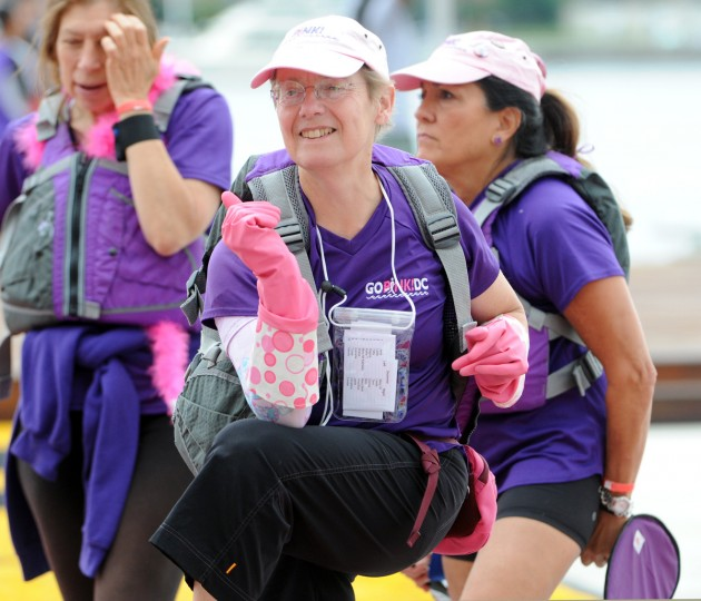 "Leslie Caplan, D.C., stretches, while wearing pink rubber gloves ""for fun"". She is a member of Go Pink DC, a dragon boat team of breast cancer survivors and supporters. They are warming up before a 500 meter time trial in the 2014 Baltimore Dragon Boat Challenge. (Kim Hairston/Baltimore Sun)"