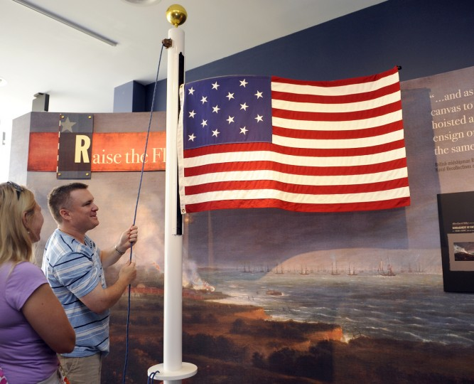 Mike Watts and his wife Devyon of Electra, TX try one of the displays, which raises and lowers a flag, at the Flag House and Star-Spangled Banner Museum. (Barbara Haddock Taylor/Baltimore Sun)