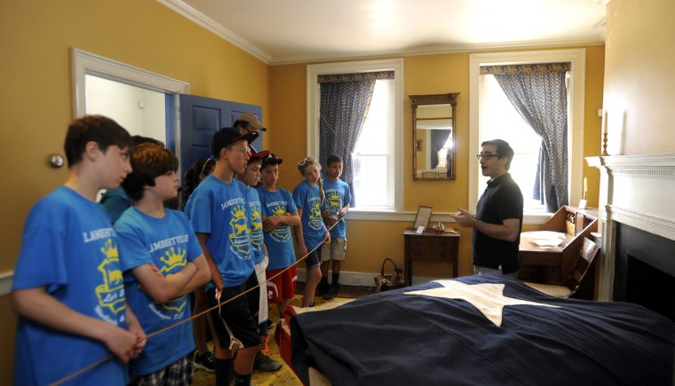 Brian Kehoe, right, a docent at the Flag House and Star-Spangled Banner Museum, speaks to a group of 6th graders from New Jersey. They are standing in the front room of Flag House, where Mary Pickersgill sewed the flag that flew over Fort McHenry and inspired the national anthem. (Barbara Haddock Taylor/Baltimore Sun)