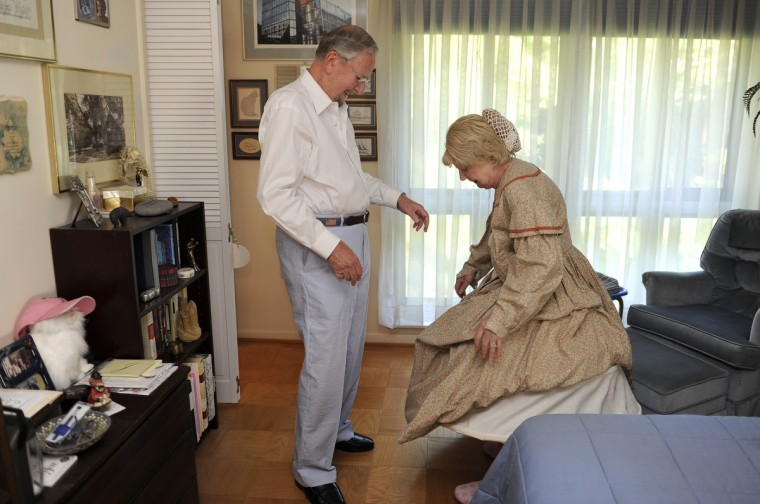 Alan Walden, left, smiles as he helps his wife of 35 years, Jeannie Walden, get into her replica of an 1860s era hoop dress. Jeannie Walden has been portraying a woman of the Civil War era for Memorial Day and other patriotic observances for the last 25 years. (Barbara Haddock Taylor/Baltimore Sun)