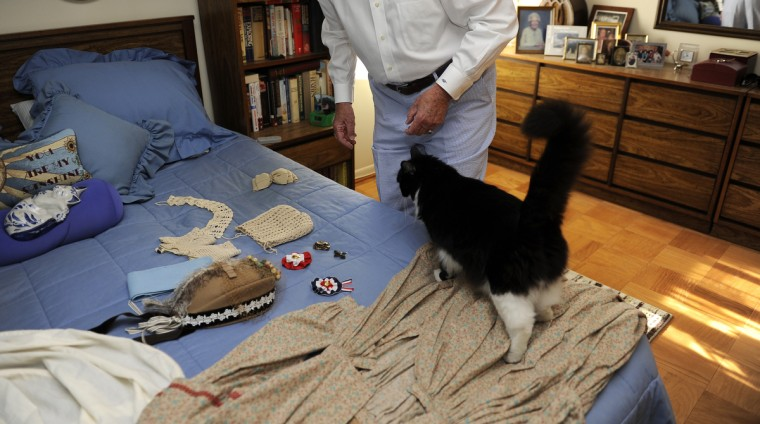 Mr. Boots the cat, walks around the bed where Jeannie Walden's Civil War widow costume is laid out on the bed. Alan Walden, right, Jeannie's husband, helps her put on the costume every time. (Barbara Haddock Taylor/Baltimore Sun)