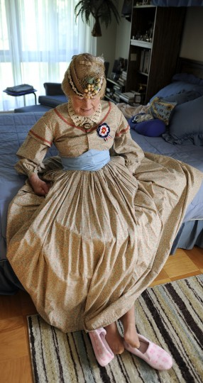 Jeannie Walden, who is 81, has been portraying a woman of the Civil War era for Memorial Day and other patriotic observances for the last 25 years. Here, she kicks off her bedroom slippers before putting on the shoes that she'll wear to the Memorial Day Observance at Dulaney Valley Gardens. (Barbara Haddock Taylor/Baltimore Sun)