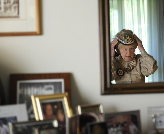 Jeannie Walden, who is 81, checks her costume in a mirror. She has been portraying a woman of the Civil War era for Memorial Day and other patriotic observances for the last 25 years. (Barbara Haddock Taylor/Baltimore Sun)