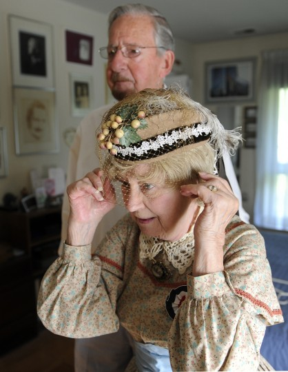 Alan Walden, left, watches as his wife of 35 years, Jeannie Walden, checks her hat in a mirror at their home. (Barbara Haddock Taylor/Baltimore Sun)