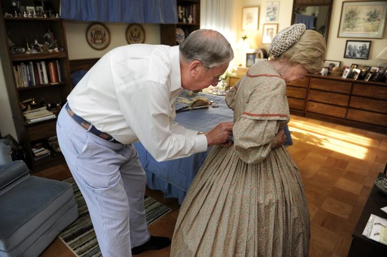 Alan Walden, left, helps his wife of 35 years, Jeannie Walden, get into her replica of an 1860s era hoop dress. (Barbara Haddock Taylor/Baltimore Sun)