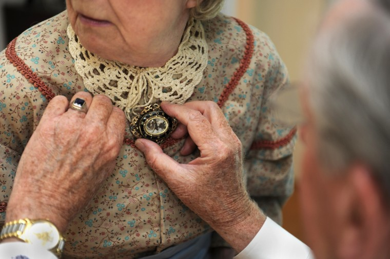 Alan Walden places an authentic 1861 widow's pin on his wife Jeannie's costume. (Barbara Haddock Taylor/Baltimore Sun)
