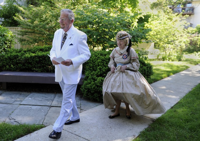 Alan Walden, left, and his wife of 35 years, Jeannie Walden, walk to their car on their way to the annual Memorial Day Observance at Dulaney Valley Gardens. Jeannie is wearing an 1860s era hoop dress and has been portraying a woman of the Civil War era for patriotic observances for the last 25 years. (Barbara Haddock Taylor/Baltimore Sun)
