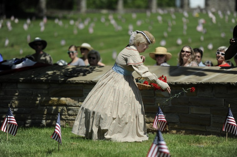 Jeannie Walden, who has been portraying a Civil War era widow at the annual Memorial Day Observance at Dulaney Valley Memorial Gardens for 25 years, places flowers on soldiers' graves during the ceremony. (Barbara Haddock Taylor/Baltimore Sun)