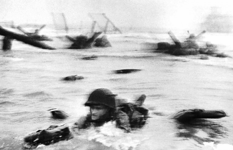 An American soldier wades through water under heavy artillery and machine-gun fire to reach the beach on the Normandy coast of France on June 6, 1944. It turned out to be the biggest and most important Allied amphibious operation of World War II. (Wartime Pool/Robert Capa)