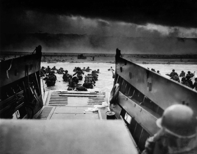 American GIs wade into the Normandy surf on June 6, 1944 during the Allied D-Day invasion. The troops, exiting off a U.S. Coast Guard landing craft, were met by intense German machine gun fire as they began their assault of the French coastline. (Robert Sargent/US Coast Guard file photo)