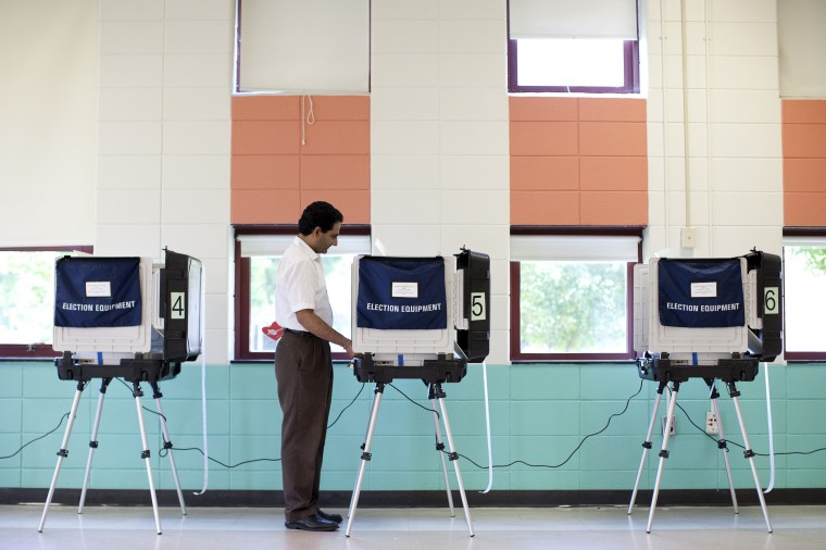 Deepak Deshpande of Ellicott City votes at Hollifield Station Elementary in Ellicott City on Tuesday, June 24, 2014. (Jen Rynda/BSMG)