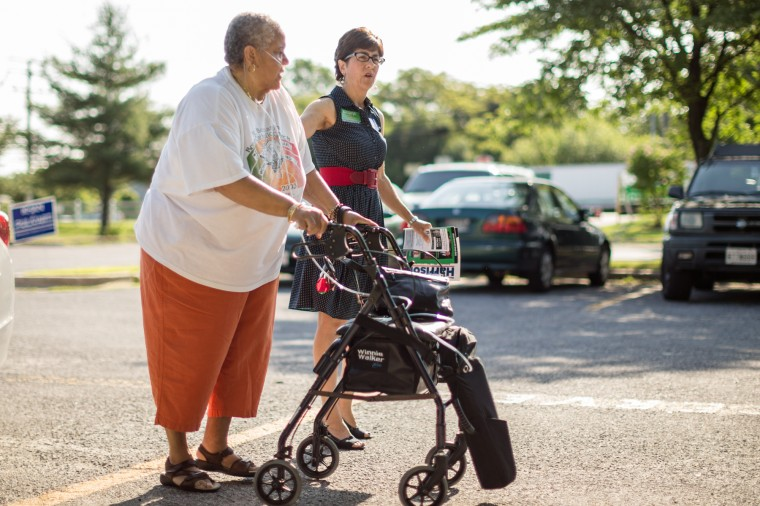 Mary Lehman, for County Council in District 1, walks with senior voter Phyllis Jackson, of Laurel, a resident of Parkview Senior Apartments, outside of Oaklands Elementary School. (Nate Pesce/BSMG)