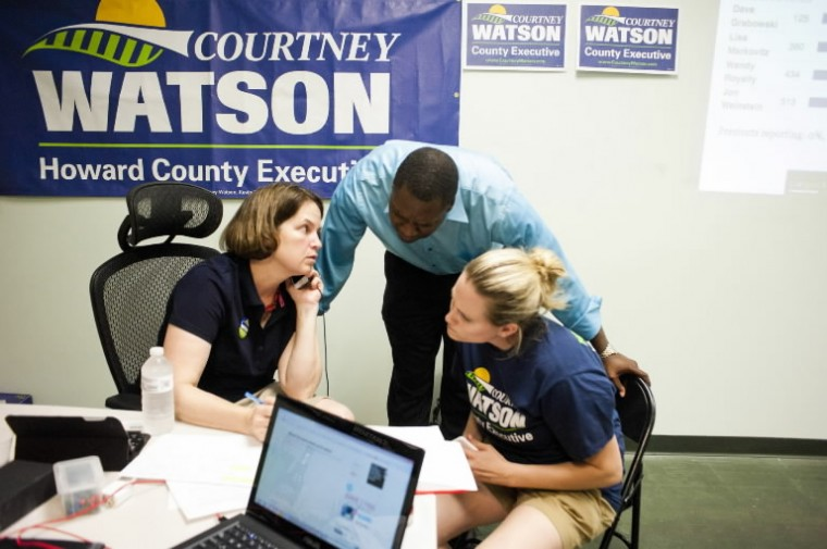 Courtney Watson and her campaign manager, Anna Mudd, talk with County Councilman Calvin Ball as primary election numbers come in at the Brown/Ulman headquarters in Columbia. (Noah Scialom/BSMG)