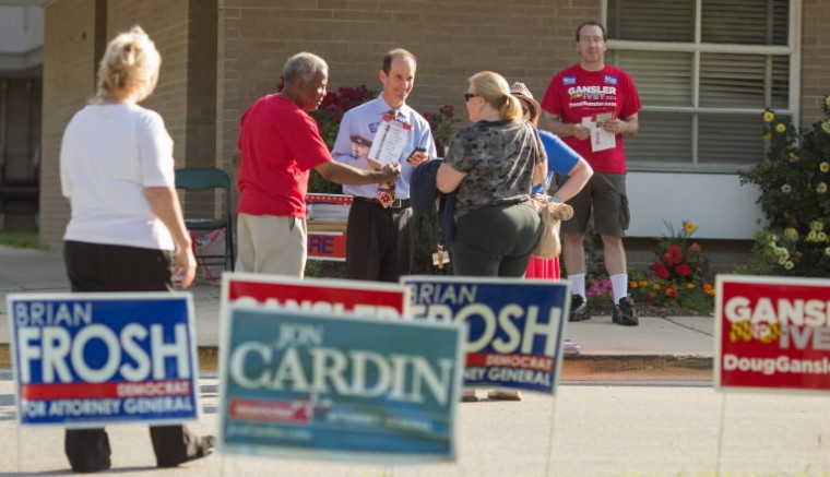 Jon Cardin, candidate for Attorney General, center in blue, campaigns to voters making their way into Bond Mill Elementary School.