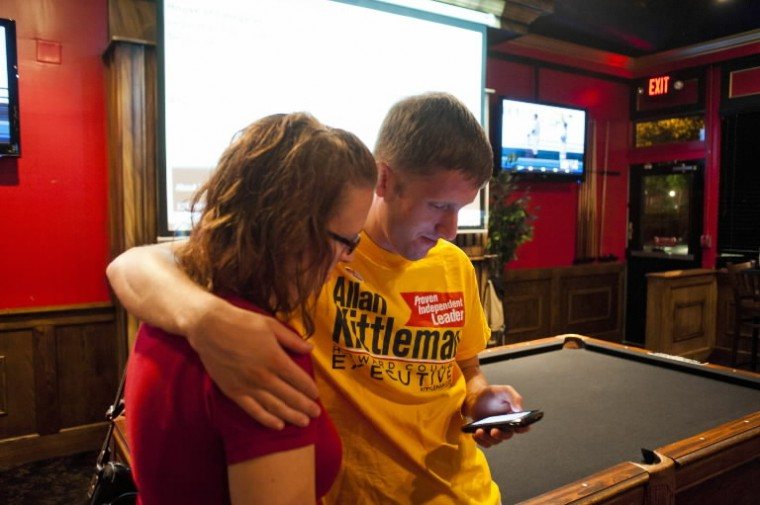 Kevin Rodkey and his wife, Erica, of Columbia, check primary election results on his phone as they are simultaneously projected on the wall behind them at Union Jacks in Columbia on Tuesday, June 24. (Noah Scialom/BSMG)