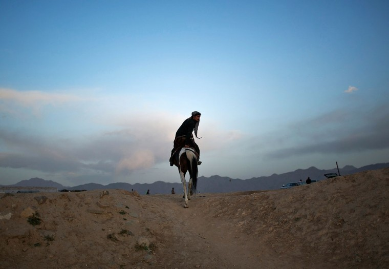 An Afghan man rides a horse as he heads home at the end of a day in Kabul June 5, 2014. (Ahmad Masood/Reuters)