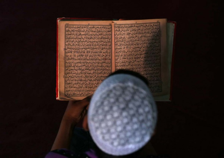 An Afghan boy reads the Koran in a madrasa, or religious school, during the Muslim holy month of Ramadan in Kabul June 30, 2014. (Mohammad Ismail/Reuters)