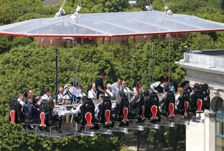 "Guests and cooks enjoy a ""Dinner in the Sky"" on a platform hanging in front of Cinquantenaire park in Brussels June 2, 2014. ""Dinner in the Sky"" accommodates 22 guests, seated at a table suspended from a crane at a height of 40 metres (131 ft.). (Yves Herman/Reuters)"