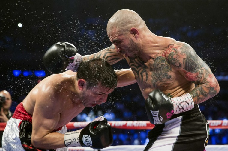 Miguel Cotto lands a punch on Sergio Martinez in the 8th round of their WBC middleweight title bout at Madison Square Garden in New York June 7, 2014. Cotto defeated Martinez in the 9th round. (Brendan McDermid/Reuters)