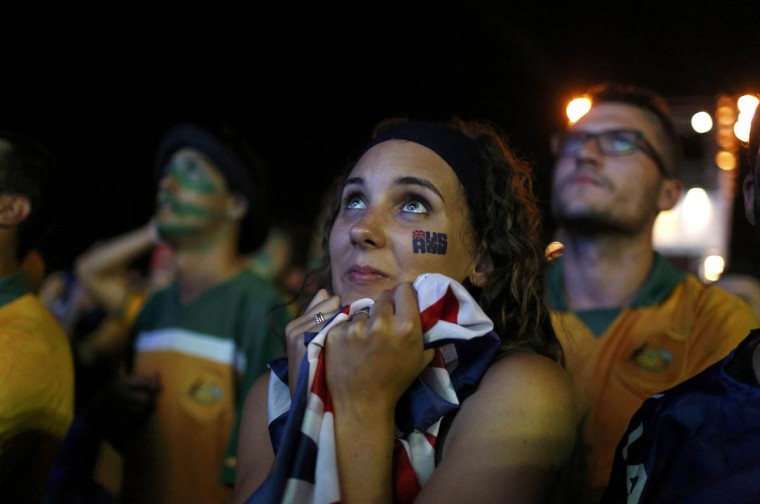 An Australian soccer fan embraces a flag as she watches the 2014 World Cup soccer match between Chile and Australia which was broadcast on a large screen at Copacabana beach in Rio de Janeiro. (Pilar Olivares/Reuters photo)