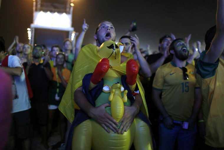 An Australian soccer fan holds an inflatable kangaroo as he watches the 2014 World Cup soccer match between Chile and Australia which was broadcast on a large screen at Copacabana beach in Rio de Janeiro June 13, 2014. (Pilar Olivares/Reuters photo)
