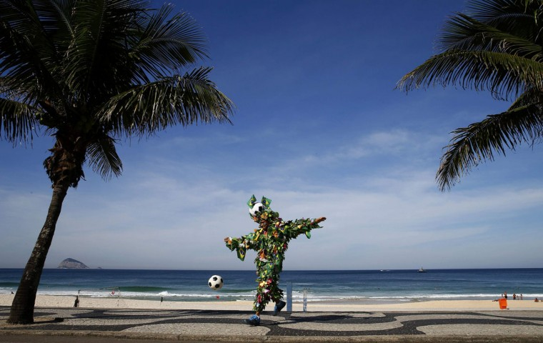 A Brazilian football fan plays with a soccer ball as he poses for a photograph on a beach in Rio de Janeiro June 8, 2014. The 2014 World Cup in Brazil starts on June 12. (Eddie Keogh/Reuters)