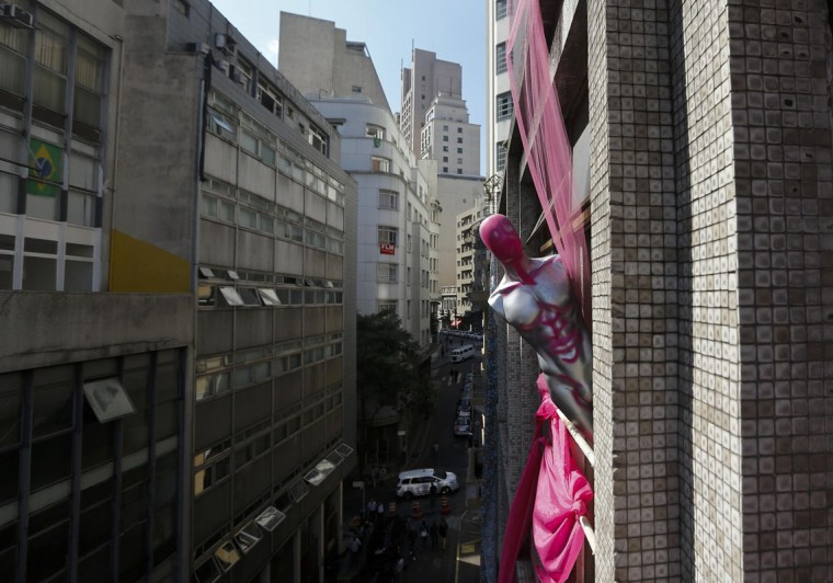 A dummy is sticked out of the window as a part of installation in an abandoned office building, occupied by squatters, in the centre of Sao Paulo, June 18, 2014. This building located in Sao Paulo downtown was abandoned for twelve years and occupied by squatters about two months ago. According to City Hall, there are some 400,000 people in need of stable housing, including some 4,000 families who are members of the Roofless Movement, and are squatting in abandoned or vacant buildings from apartment blocks to hotels in Sao Paulo, the largest city in South America. Picture taken June 18, 2014. (Maxim Shemetov/Reuters)