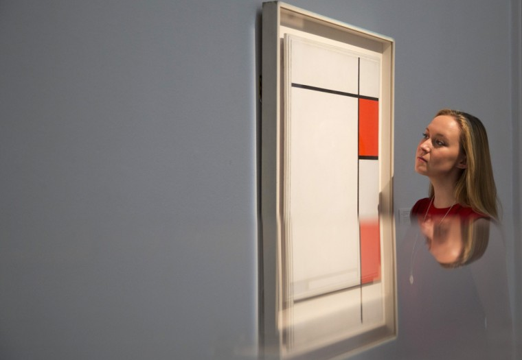 A gallery assistant is reflected as she views the work Composition with Red, Blue and Grey by Piet Mondrian during a photo-call for Impressionist and Modern Art Evening Sale at Sotheby's auction house in London. (Neil Hall/Reuters)