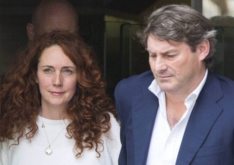 Former News International chief executive Rebekah Brooks and her husband Charlie leave the Old Bailey courthouse in London June 24, 2014. Rebekah Brooks, the former boss of Rupert Murdoch's British newspaper arm, was acquitted on Tuesday of orchestrating a campaign to hack into phones and bribe officials in the hunt for exclusive news. (REUTERS/Neil Hall)