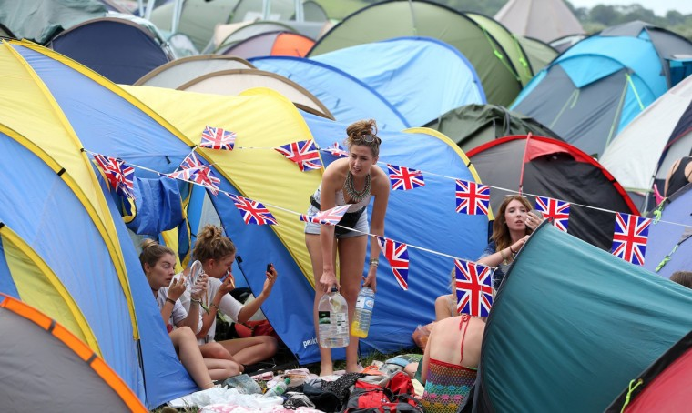 Festival goers fix their makeup at Worthy Farm in Somerset on the second day of the Glastonbury music festival June 26, 2014. (Cathal McNaughton/Reuters)