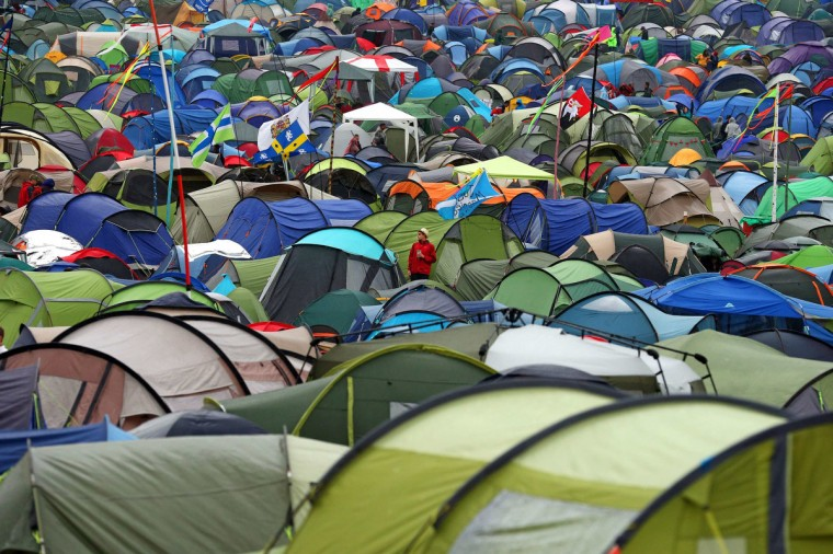 A festival goer stands amongst the tents at Worthy Farm in Somerset, on the second day of the Glastonbury music festival June 26, 2014. (Cathal McNaughton/Reuters)