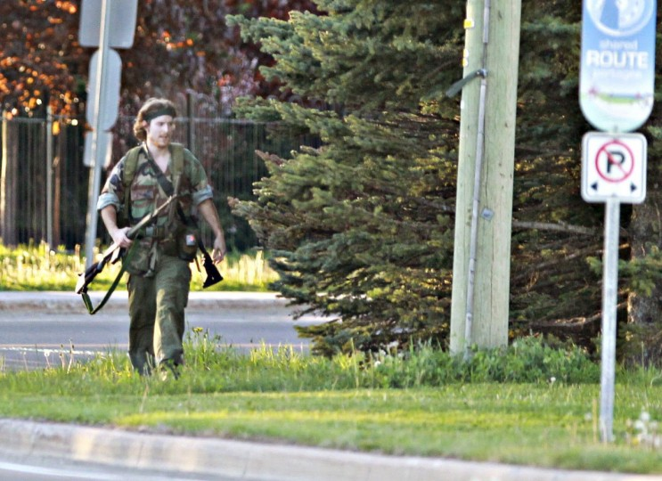 A heavily armed man that police have identified as Justin Bourque walks on Hildegard Drive in Moncton, New Brunswick June 4, 2014 after several shots were fired in the area. Three police officers were shot dead and two more were wounded, police said, as they conducted a manhunt for a man carrying a rifle and wearing camouflage clothes. Police said they were searching for Justin Bourque, 24, of Moncton. Picture taken June 4, 2014. (Viktor Pivovarov/Times & Transcript/telegraphjournal.com/Reuters)