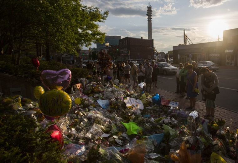 People look at the memorial on the steps of Royal Canadian Mounted Police Headquarters (RCMP) headquarters in Moncton, New Brunswick, June 9, 2014. A 24-year-old man was charged with murder on Friday in the slayings of three Royal Canadian Mounted Police officers during a shooting spree in the eastern Canadian city of Moncton. (Mark Blinch/Reuters)