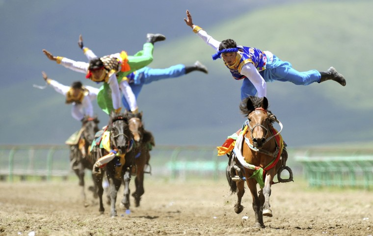 Tibetan participants perform on horses during a traditional equestrian competition in Hongyuan county of Aba Tibetan and Qiang Autonomous Prefecture, Sichuan Province. (China Daily/Reuters)