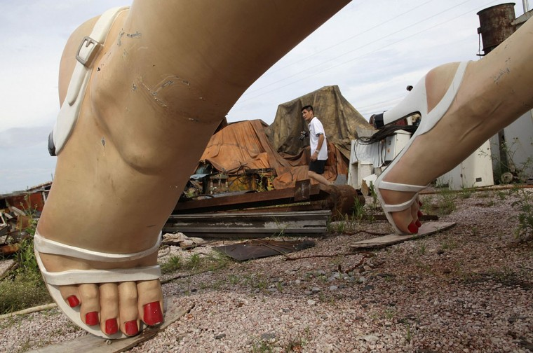 "A man walks past the feet of a giant statue of U.S. actress Marilyn Monroe at the dump site of a garbage collecting company in Guigang, Guangxi Zhuang Autonomous Region June 18, 2014. The eight-metre-tall stainless steel statue, which weighs about eight tonnes, was made by several Chinese artists for over two years, based on the famous scene from her movie ""The Seven Year Itch"". The statue was transported to the garbage collecting company early this week for unknown reasons after being showed outside a business centre in the city for only 6 months, local media reported. (China Daily/Reuters)"