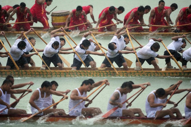 Participants paddle dragon boats during a competition amid heavy rainfall to celebrate the Dragon Boat Festival in Tongren, Guizhou province June 2, 2014. The festival is commemorated in memory of Chinese patriotic poet Qu Yuan, who drowned himself on the day in 277 B.C. (China Daily/Reuters)