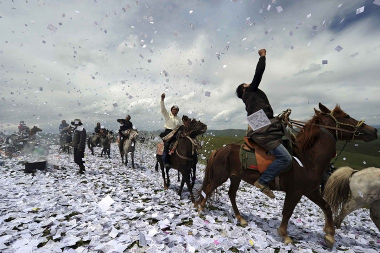 "Tibetans throw praying papers on horseback as they gather for a traditional praying festival called ""Wei Sang"", in Hongyuan county of Aba Tibetan and Qiang Autonomous Prefecture, Sichuan province June 18, 2014. The festival is usually held in every May or June, when Tibetans burn tree branches to create smoke and throw praying papers to wish for good fortunes and a better pasture season. Picture taken June 18, 2014. (China Daily/Reuters)"