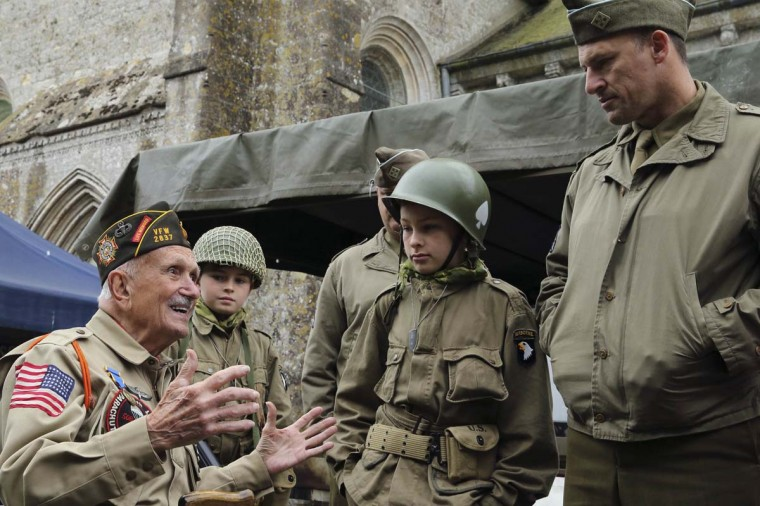 U.S. World War II veteran Jack W. Schlegel (L), 91 years-old from Mount Tremper, New York, who served with the 508 PIR, 82nd Airborne, speaks to history enthusiasts in Sainte-Marie-du- Mont, June 3, 2014. Schlegel parachuted onto the Normandy coast in the early hours of June 6, 1944. World leaders will attend ceremonies in Normandy June 6, marking the 70th anniversary of the allied beach landings on D-Day.    || PHOTO CREDIT: PASCAL ROSSIGNOL  - REUTERS