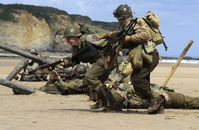 History enthusiasts wearing World War Two U.S. military uniforms re-enact a D-Day landing on Omaha Beach in Vierville sur Mer, on the coast of Normandy June 5, 2014. (Pascal Rossignol/Reuters)