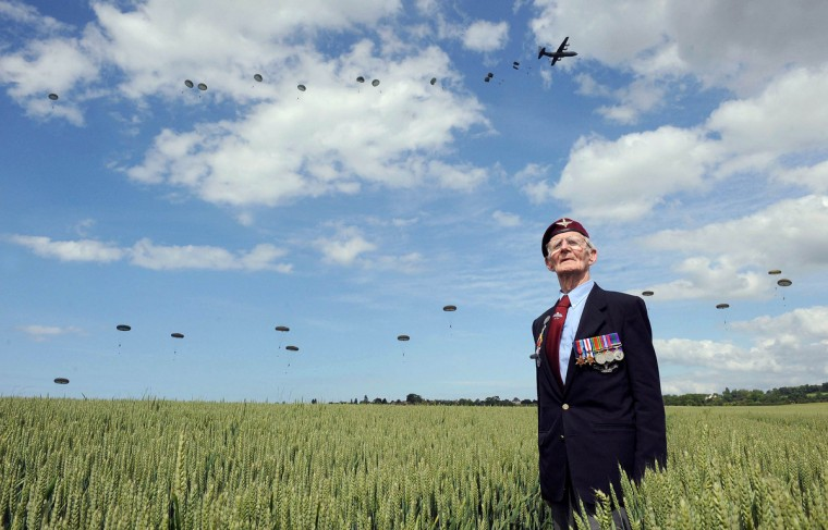 British World War II veteran Frederick Glover poses for a photograph as soldiers parachute down during a D-Day commemoration paratroopers launch event in Ranville, northern France, June 5, 2014. (Thomas Bregardis/Reuters)
