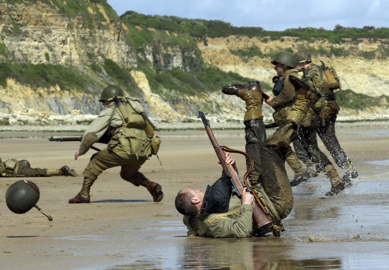 History enthusiasts wearing WW2 U.S. military uniforms re-enact a D-Day landing on Omaha Beach in Viervill-sur-Mer, on the Normandy coast June 5, 2014. (Pascal Rossignol/Reuters)