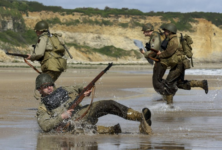 History enthusiasts wearing WW2 U.S. military uniforms re-enact a D-Day landing on Omaha Beach in Vierville-sur-Mer, on the Normandy coast June 5, 2014. (Pascal Rossignol/Reuters)
