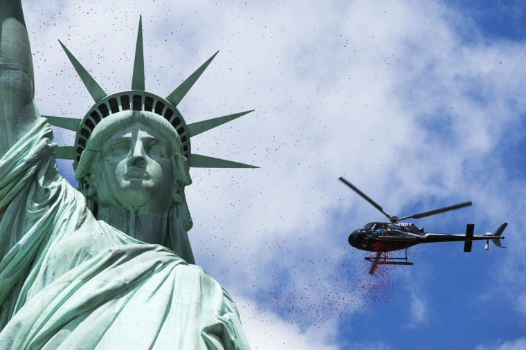 """Rose petals dropped by helicopters fall around the Statue of Liberty in New York June 6, 2014. The event was organized by the organization """"The French Will Never Forget"""" to mark the 70th anniversary of World War Two's D-Day landings. (Lucas Jackson/Reuters)"""