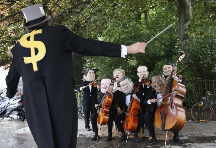 Activists dressed as musicians and wearing masks depicting leaders of the members of the G7 protest against wealth inequality outside the European Council building in Brussels June 4, 2014. The world's leading industrialized nations meet without Russia for the first time in 17 years on Wednesday, leaving President Vladimir Putin out of the talks in retaliation for his seizure of Crimea and Russia's part in destabilizing eastern Ukraine. The leaders depicted are (L-R) Japanese Prime Minister Shinzo Abe, British Prime Minister David Cameron, German Chancellor Angela Merkel, Canadian Prime Minister Stephen Harper, French President Francois Hollande, U.S. President Barack Obama and Italian Prime Minister Matteo Renzi. (Francois Lenoir/Reuters)