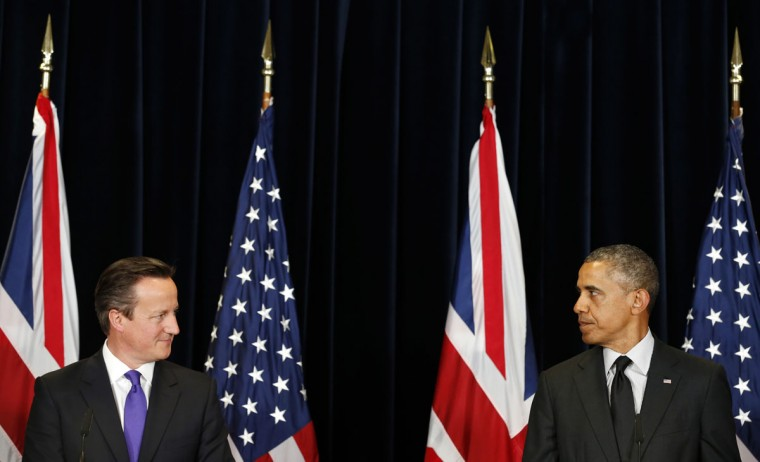 U.S. President Barack Obama (R) and British Prime Minister David Cameron look at each other as they speak at a joint news conference after their meeting at the G7 summit in Brussels June 5, 2014. (Kevin Lamarque/Reuters)