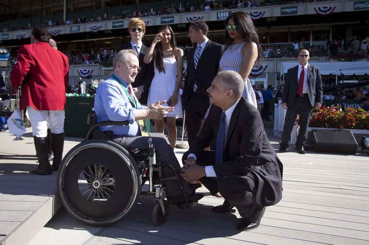 Attorney General of the United States Eric Holder (R) kneels down to speak with former jockey Ron Turcotte before the 146th running of the 2014 Belmont Stakes in Elmont, New York June 7, 2014. Turcotte rode famed horse Secretariat to the triple crown and Holder was sitting in the stand watching the race with his father in 1983. (REUTERS/Carlo Allegri)
